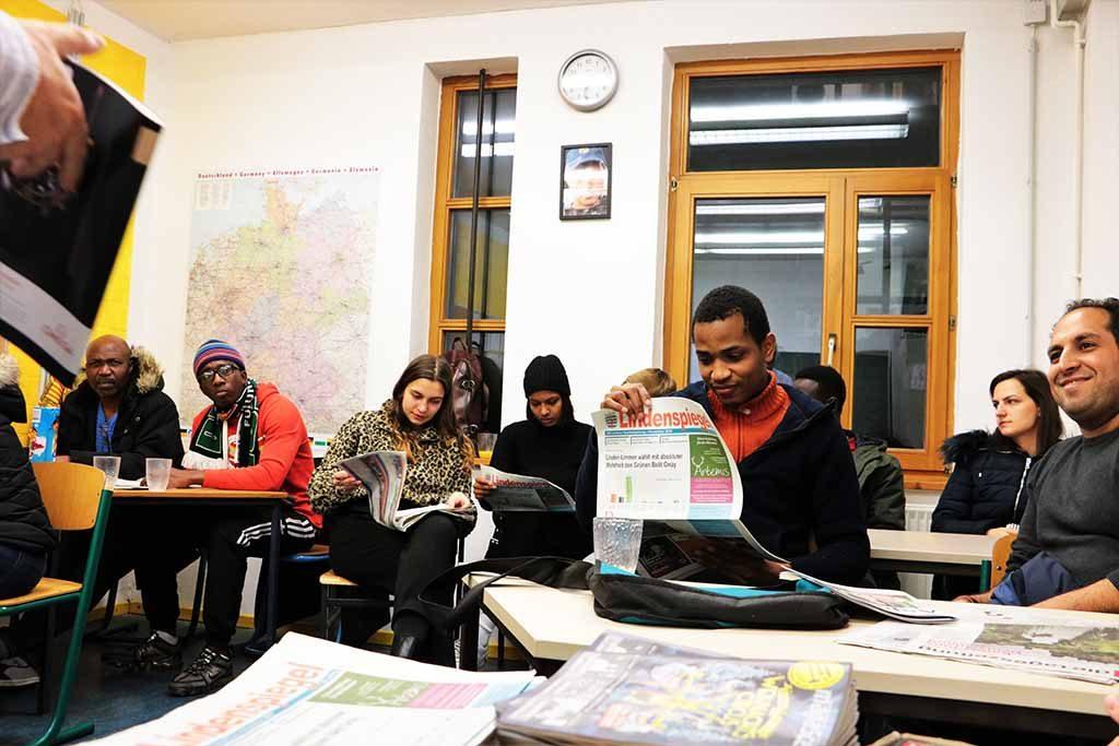 Die Gruppe sitzt an Tischen und ist in aufgeschlagene Zeitungen vertieft.