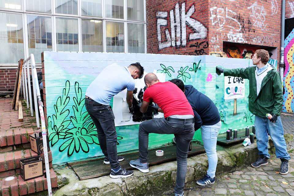 Drei Leute malen ein Bild an die Wand.