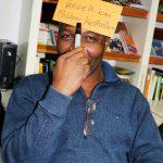 """Ein Mann hält ein Schild mit der Aufschrift """"Ärger bei der Polizeikontrolle"""" an seine Stirn."""