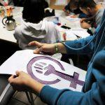 Eine Frau hält ein Bild des Symbols von Frauenpower in der Hand.
