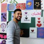 Ein Mann steht lächelnd vor einer Wand, an der viele Bilder hängen.