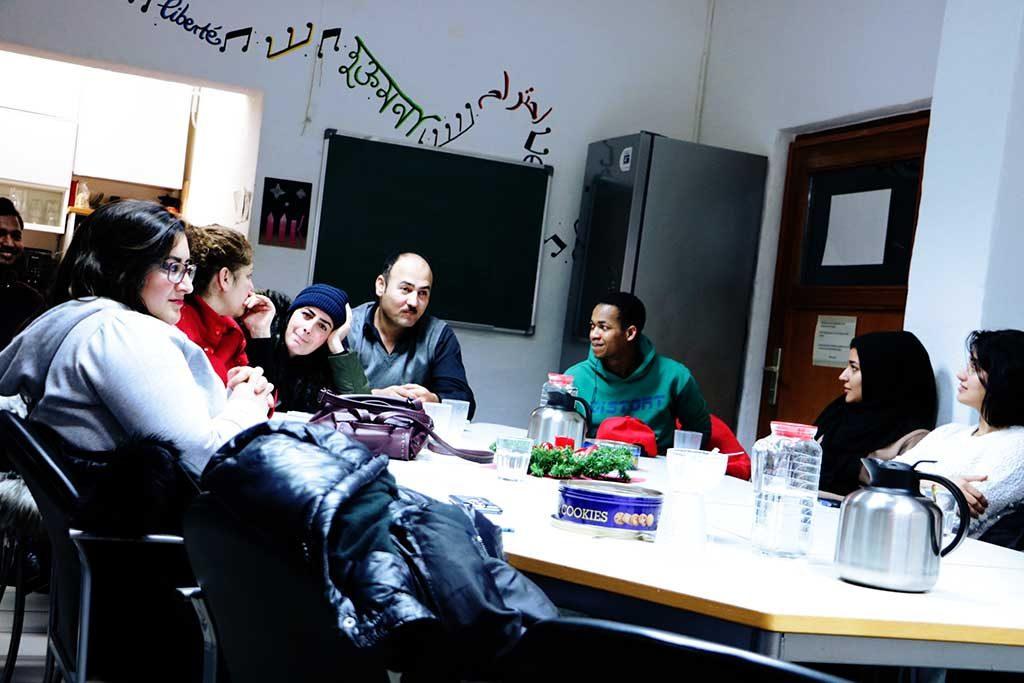 Die Gruppe ist am Tisch versammelt und diskutiert.