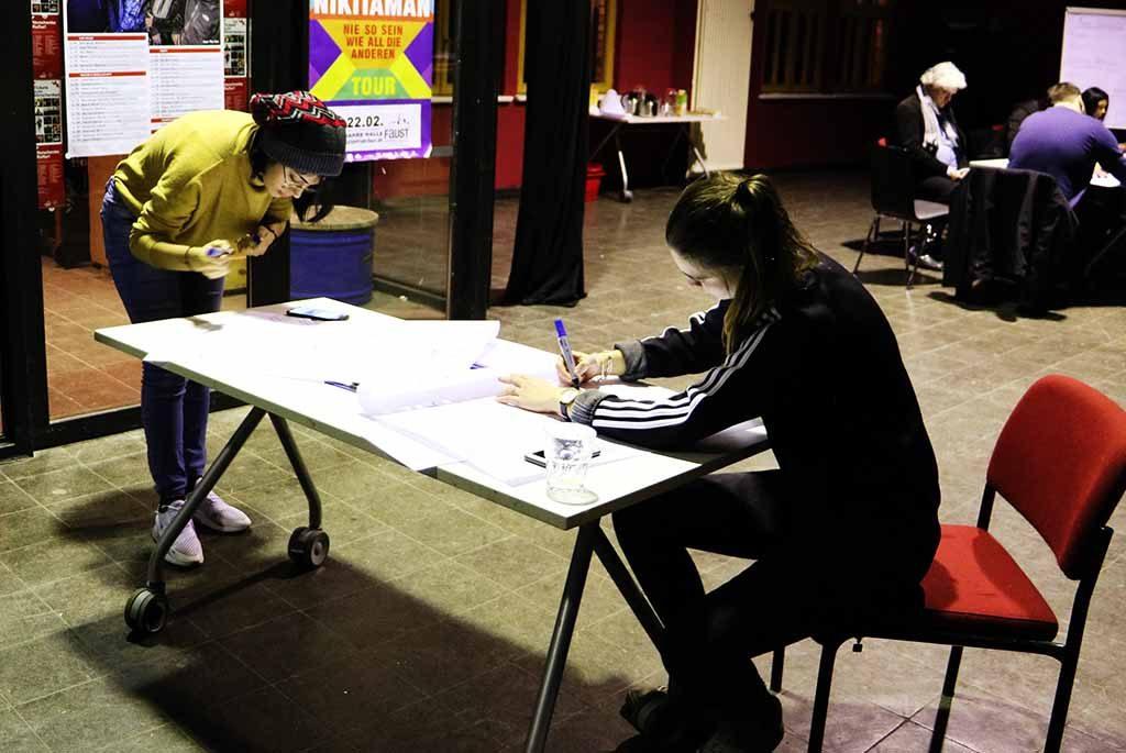 Eine Frau sitzt am Tisch und schreibt auf ein Plakat.