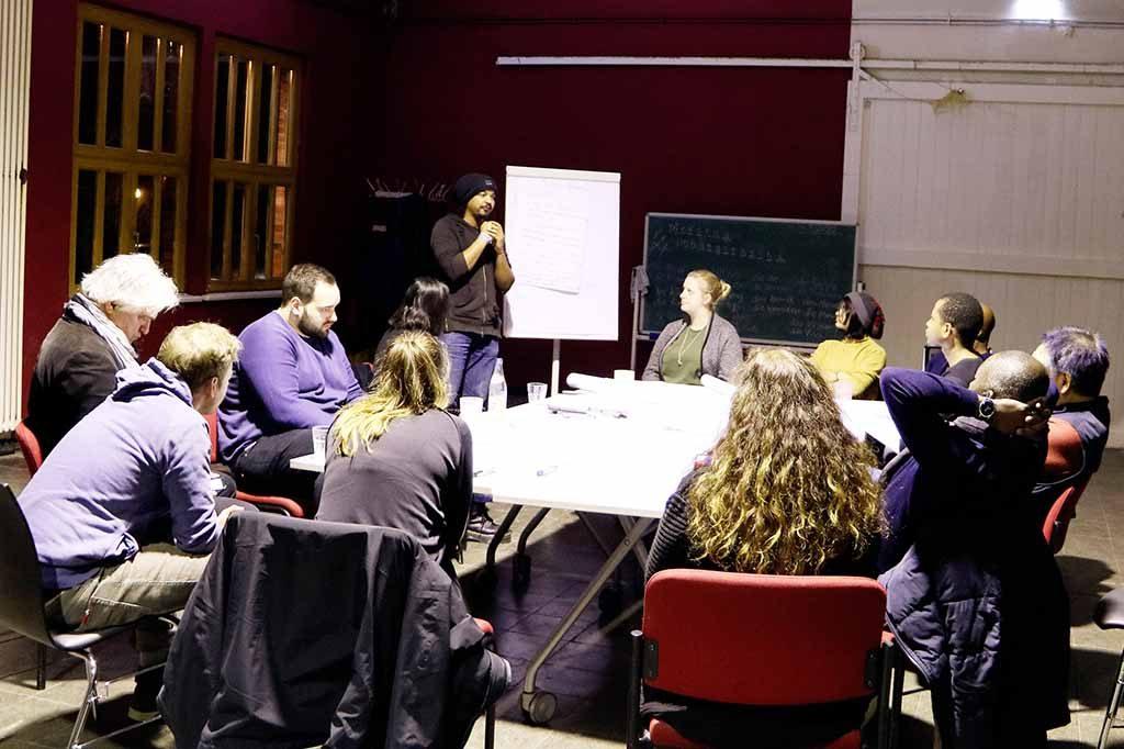 Die Gruppe sitzt am Tisch und lauscht einer Präsentation.