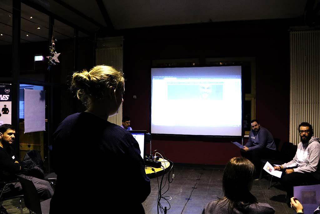 Die Gruppe schaut auf eine Leinwand, auf die ein Beamer den Bildschirminhalt projiziert.