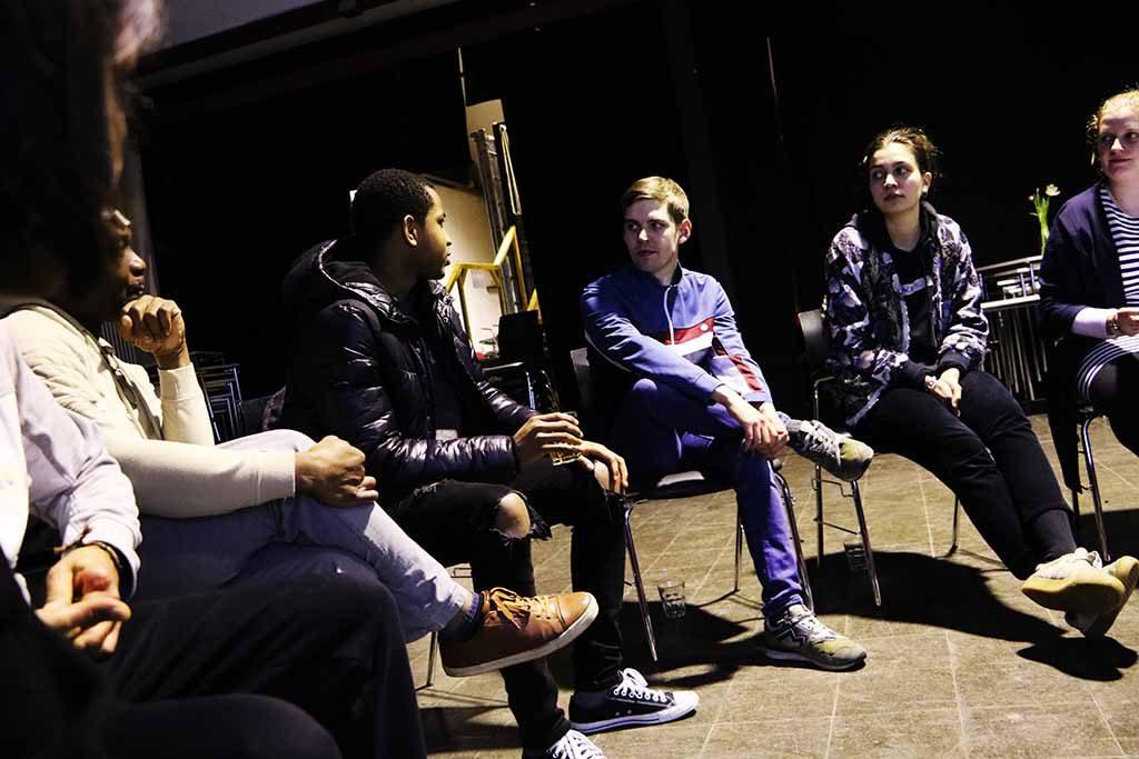 Die Gruppe sitzt und ist in eine Diskussion vertieft.