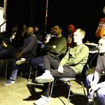 Die Gruppe sitzt auf Stühlen und schaut sich eine Präsentation an.