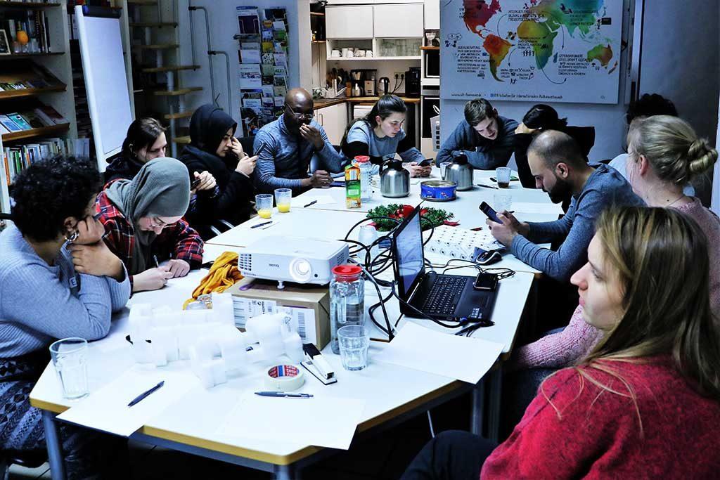 Die Gruppe sitzt am großen Tisch und hört zu.