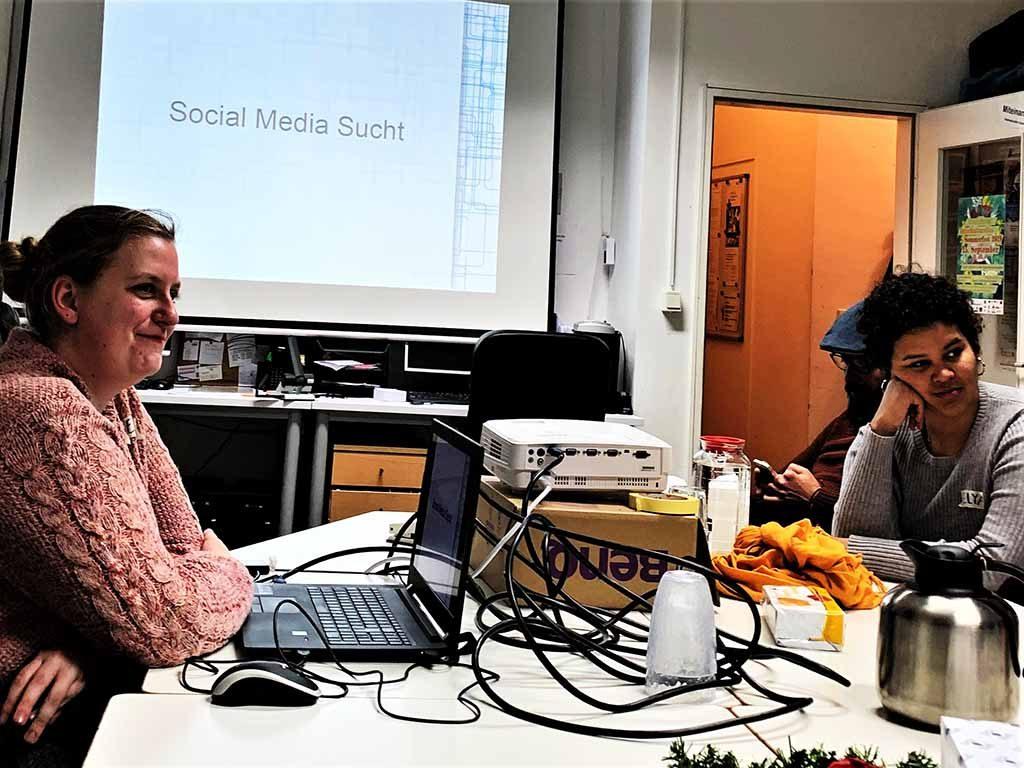 Auf einem großen Tisch sitzt ein Mann vor einem Laptop, der mit einem Beamer den Bildschirminhalt auf eine Leinwand projiziert.