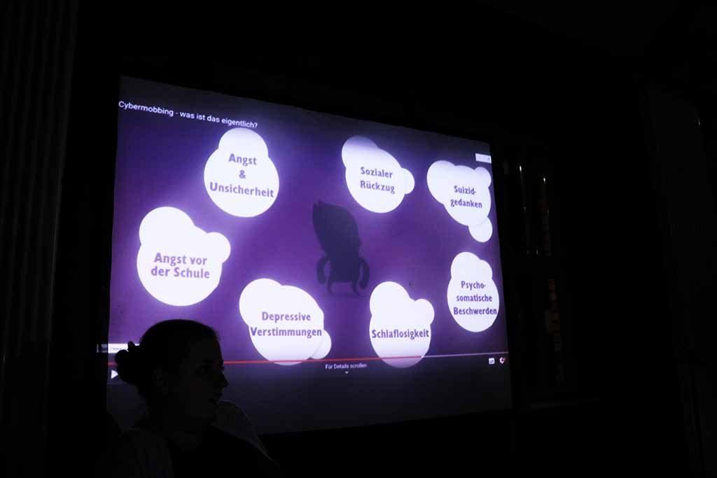 Die Gruppe schaut im Dunkeln eine Präsentation.