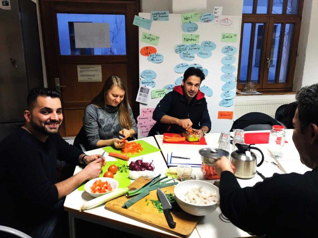 Die Gruppe sitzt an einem großen Tisch und bereitet Essen zu.