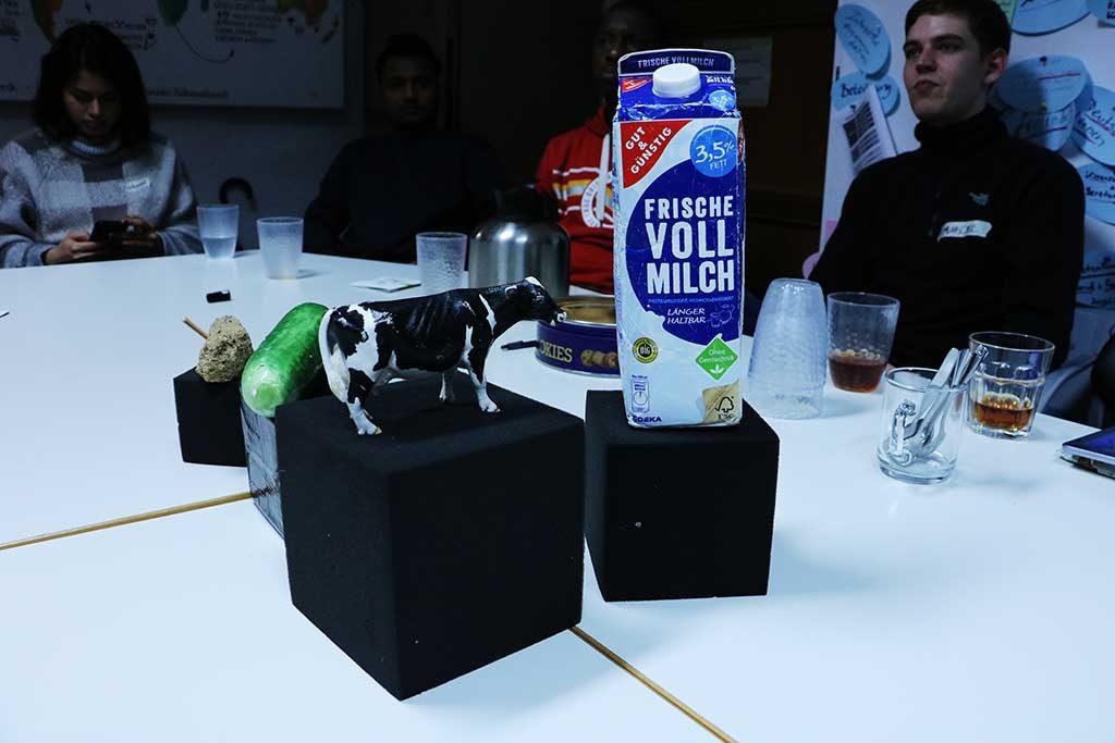 Eine Figur einer Kuh und eine Tüte Milch stehen auf einem Podest.