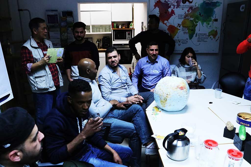 Die Gruppe sitzt am Tisch und diskutiert, auf dem Tisch liegt ein Globus.
