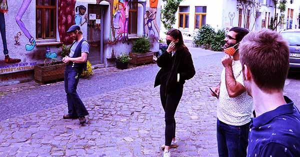 Die Gruppe trägt Masken und steht draußen mit Abstand zueinander.