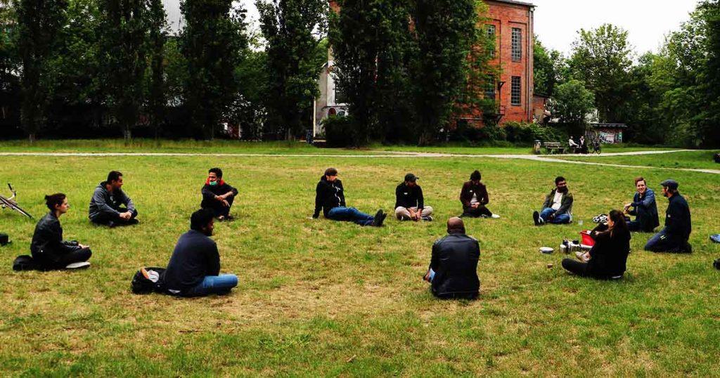 Die Gruppe sitzt weit auseinander in einem Sitzkreis auf einer Wiese.