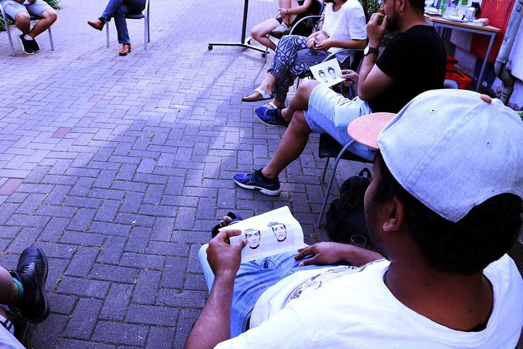 Die Gruppe sitzt draußen in einem Sitzkreis und hört zu.