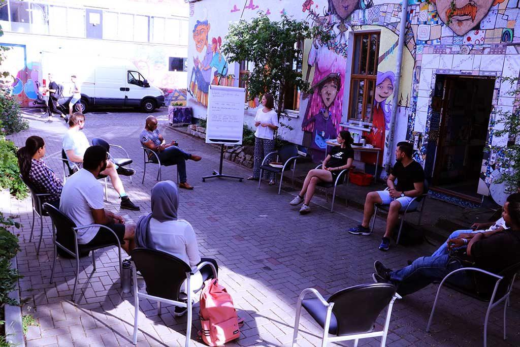 Die Gruppe ist Draußen zu einem Sitzkreis versammelt und lauscht einer Präsentation.