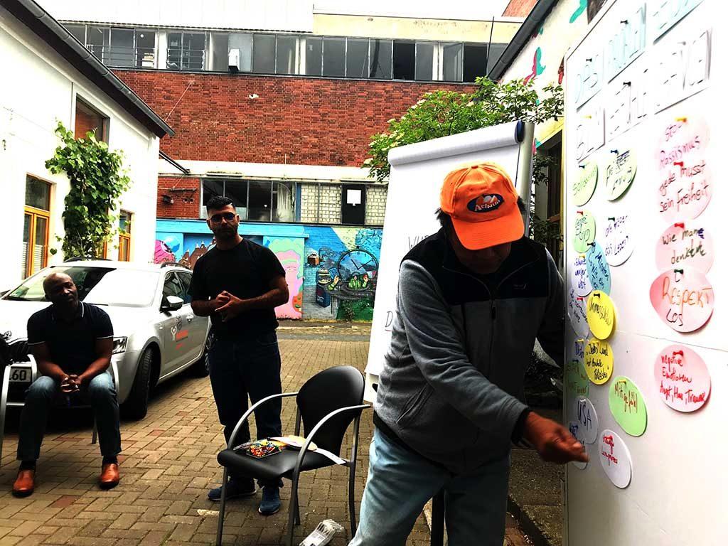 Ein junger Mann pinnt einen Zettel an eine Pinnwand.