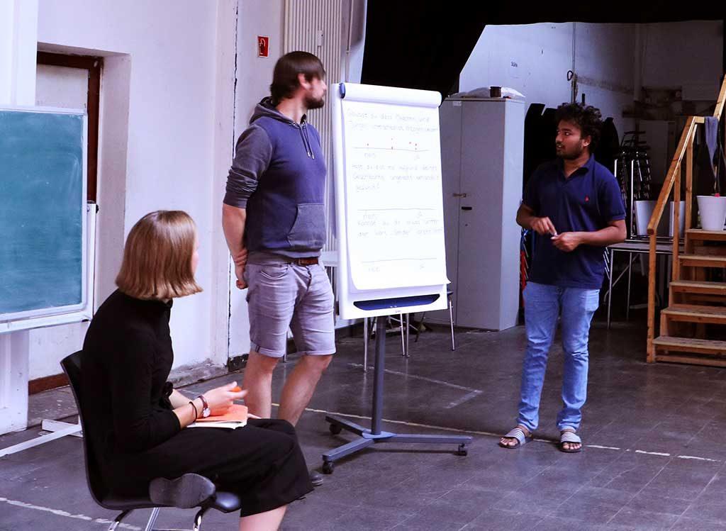 Ein junger Mann präsentiert an einem Flipboard.