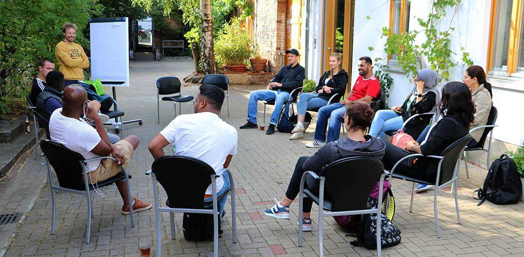 Die Gruppe sitzt im Kreis und diskutiert.