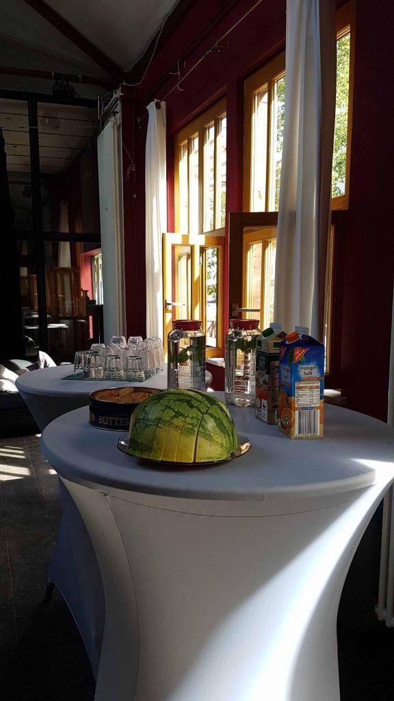 Eine aufgeschnittene halbe Melone, Getränke und leere Gläser stehen auf einem Tisch für die Teilnehmer bereit.