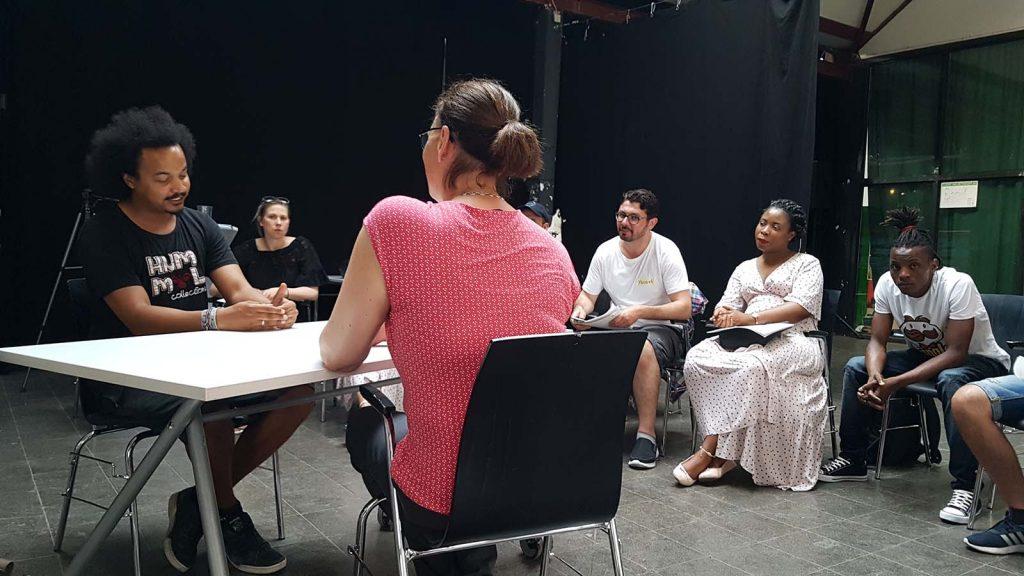 Die Gruppenleiterin sitzt mit einem der Teilnehmer am Tisch und reden, der Rest der Gruppe hört zu.