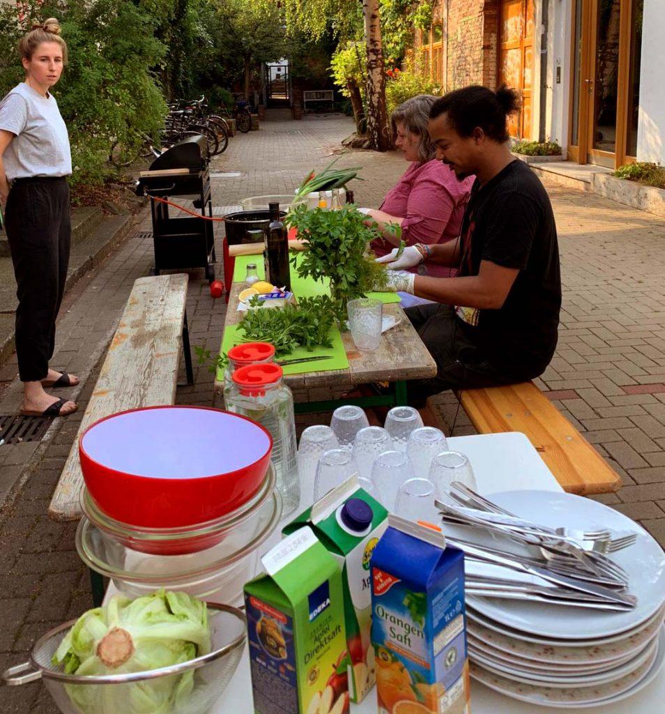 Während im Hintergrund fleißig ein Salat zubereitet wird, ist im Vordergrund das ganze Geschirr, Besteck und Zutaten für das Grillen gestapelt.