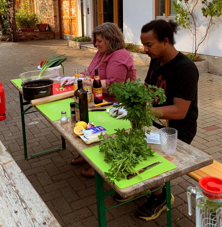 Ein Mann und eine Frau sitzen draußen am Tisch und bereiten einen Salat zu.