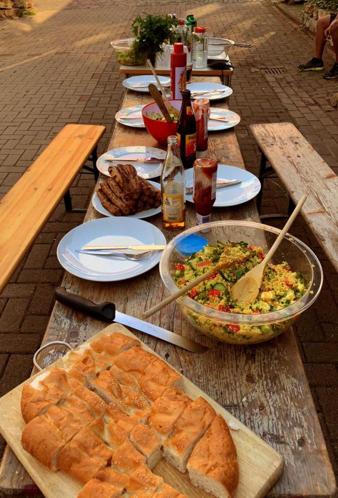 Ein frisch gedeckter Tisch mit Fladenbrot, Kuskus-Salat und einem Stapel Bratwürsten wartet auf die Gäste.