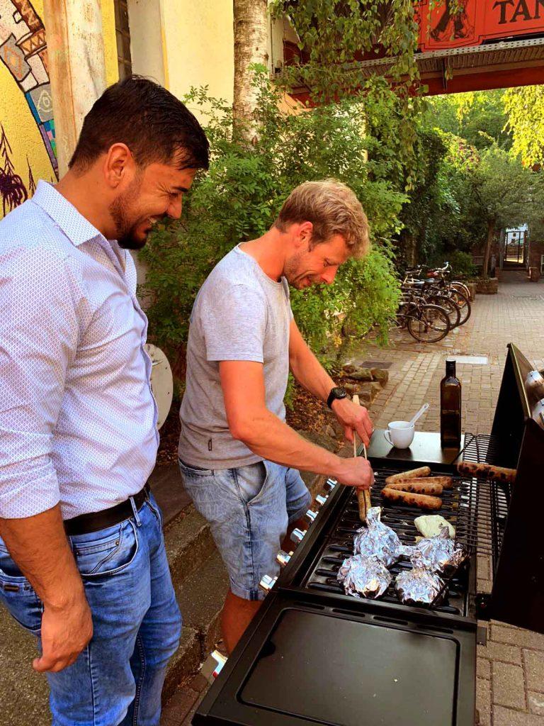 Zwei junge Männer stehen am Grill und lachen über einen Witz, während sie die Bratwürste umdrehen.