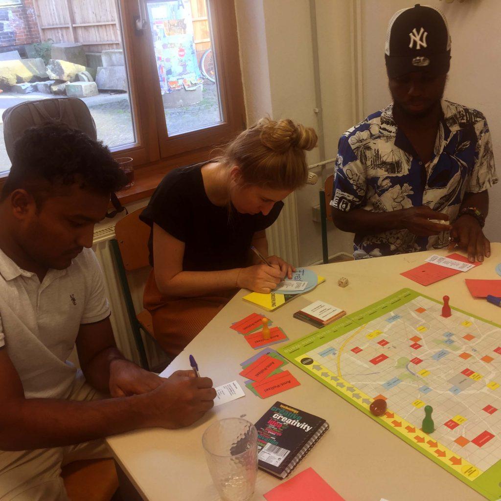 Drei Menschen spielen ein Brettspiel und schreiben dafür Notizen auf kleine Zettel.