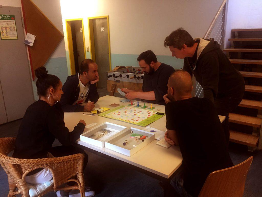 Eine Gruppe von Menschen sitzt am Tisch zusammen und bereitet sich darauf vor ein Brettspiel zu spielen.