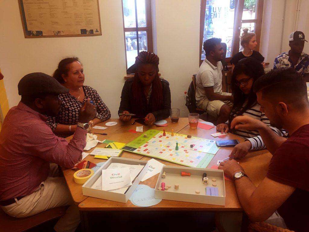 Eine Gruppe von Menschen sitzt am Tisch zusammen und spielt zusammen ein Brettspiel namens