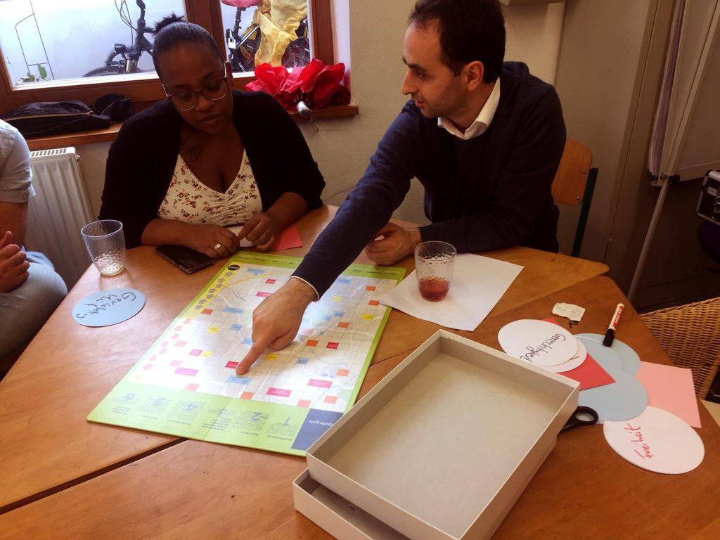 Ein Mann und eine Frau sind in ein Gespräch über ein Brettspiel vertieft. Er spricht zu ihr und zeigt mit dem Finger auf den Spielplan, während sie ihm aufmerksam zuhört.