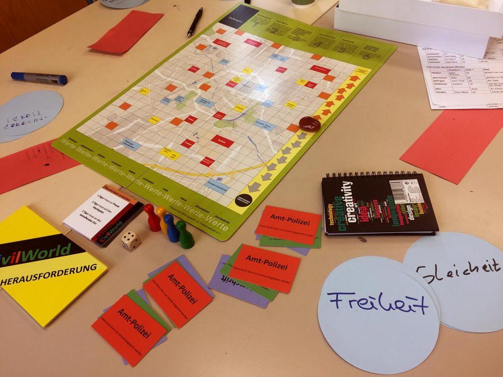 """Das Brettspiel """"Civil World"""", der Spielplan, die Spielfiguren, Karten, Anleitung und ein Würfel liegen ausgebreitet auf dem Tisch."""