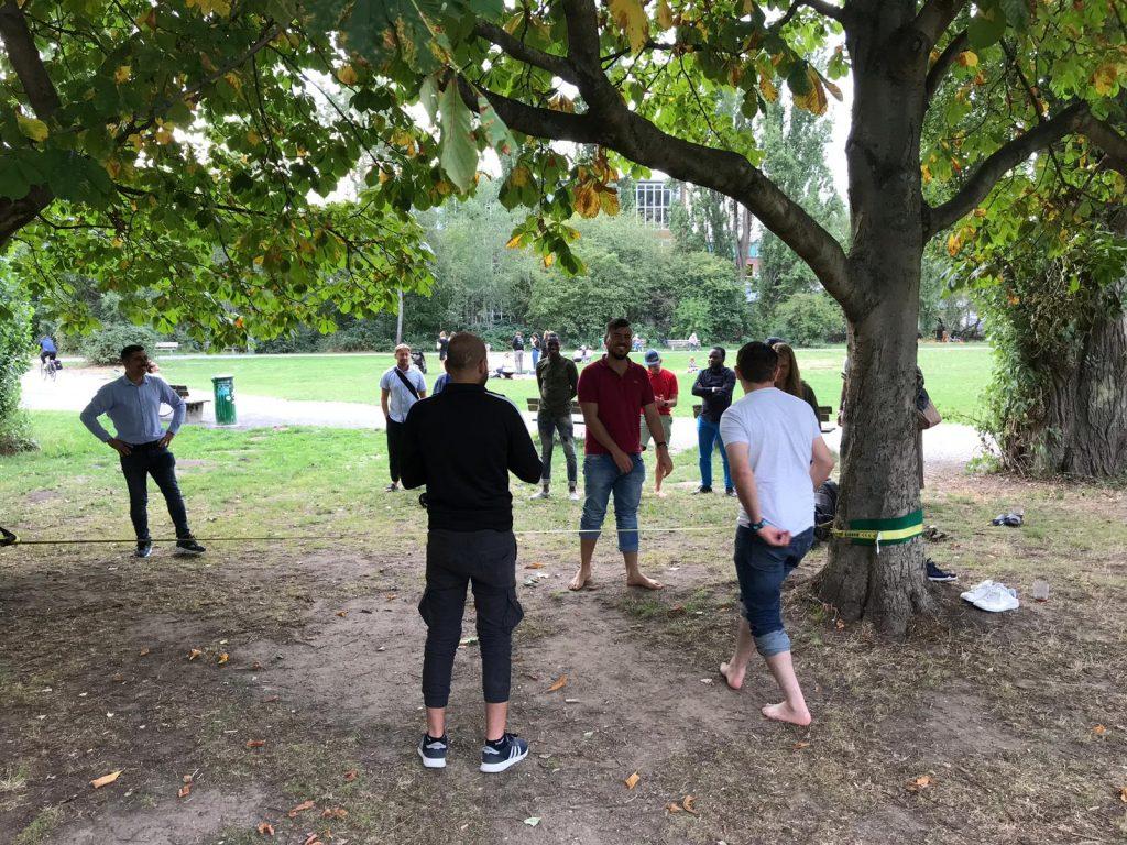 Die Gruppe steht nah an der Slackline, es wird geredet und gelacht.