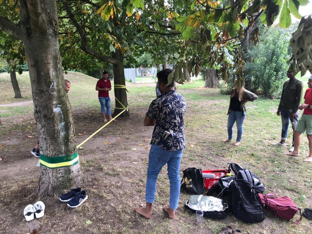 Die Teilnehmer haben sich um eine zwischen zwei Bäumen gespannte Slackline versammelt.