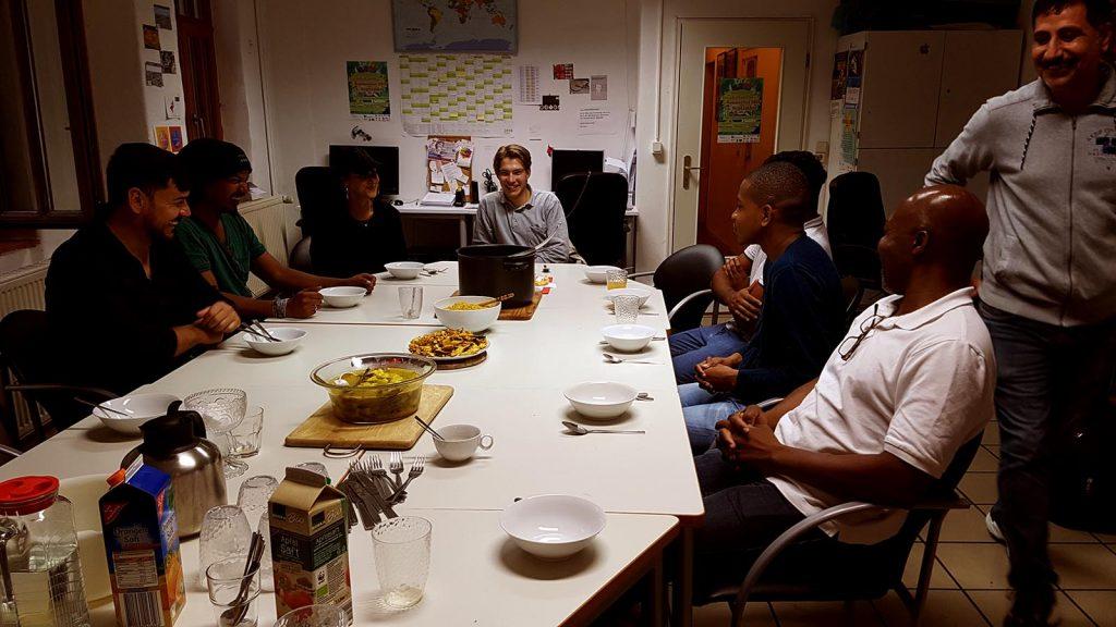 Eine Gruppe Menschen sitzt lachend am gedeckten Tisch und erwartet sehnsüchtig das Essen, das in der nahen Küche schon gut duftet.