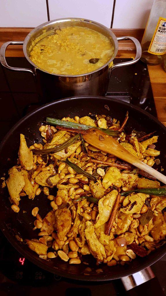 Eine brutzelnde Pfanne und ein kochender Topf stehen auf dem Herd, das essen ist fast fertig.