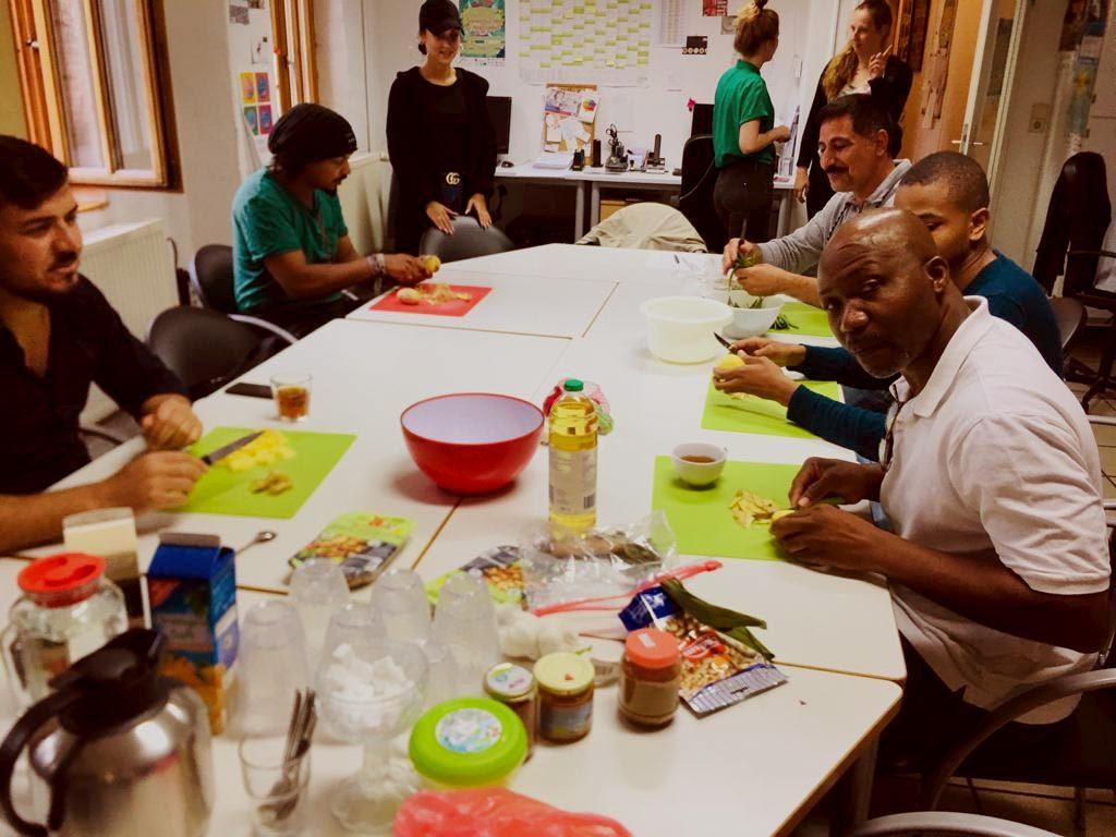 Auf einem langen Tisch sitzen viele Menschen zusammen und schneiden Gemüse. Auf dem Tisch liegen auch allerlei Besteck und Zutaten vorbereitet.