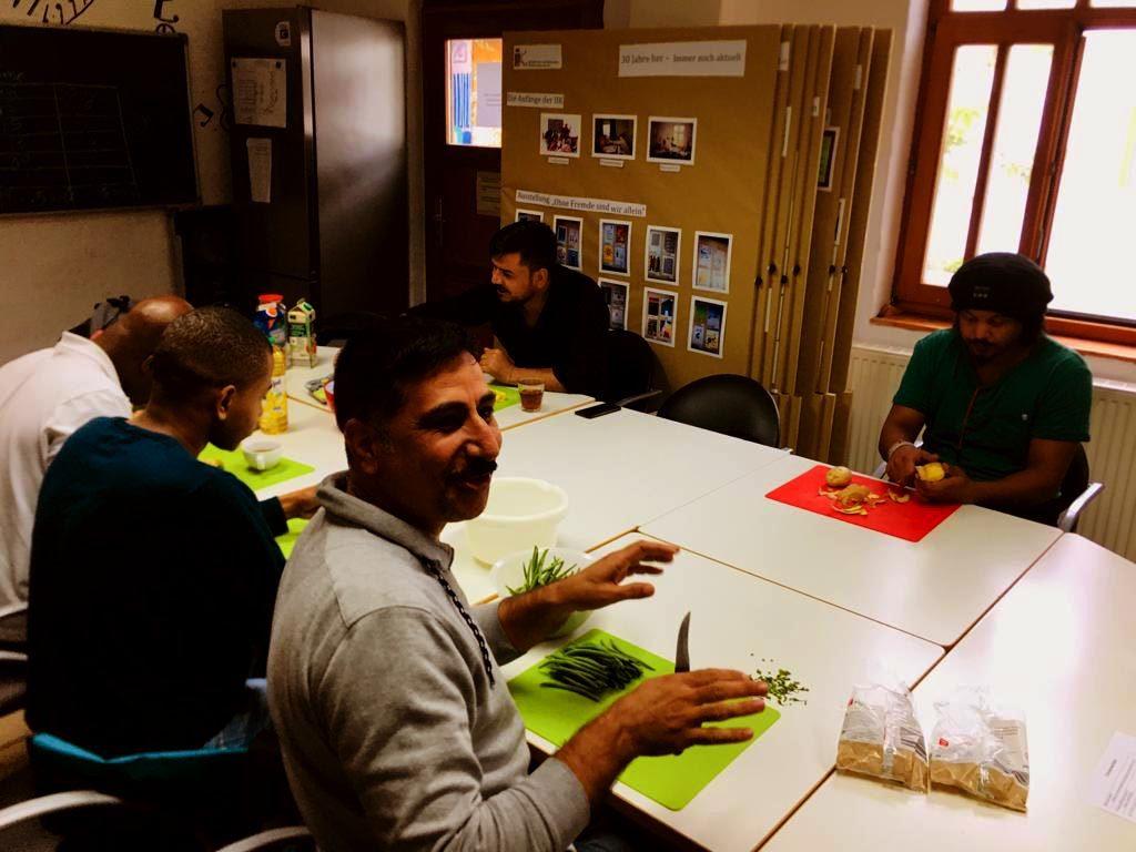 Eine Gruppe von Menschen sitzt am Tisch, schneidet Gemüse und unterhält sich dabei.