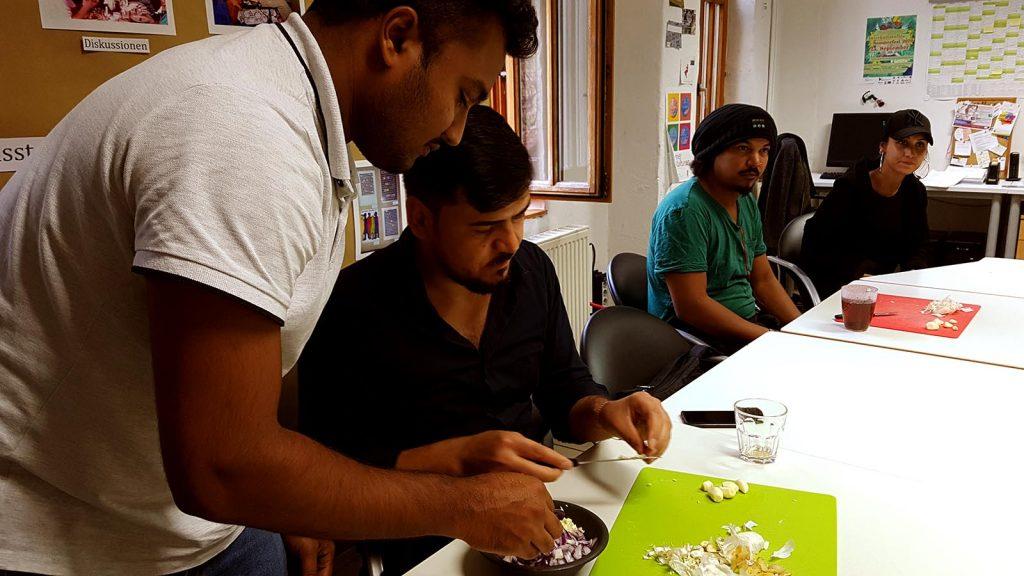 Ein junger Mann sammelt verschiedene Zutaten in einer kleinen Schale. Ein anderer Mann fügt klein geschnittenen Zwiebeln zerkleinerten Knoblauch hinzu.