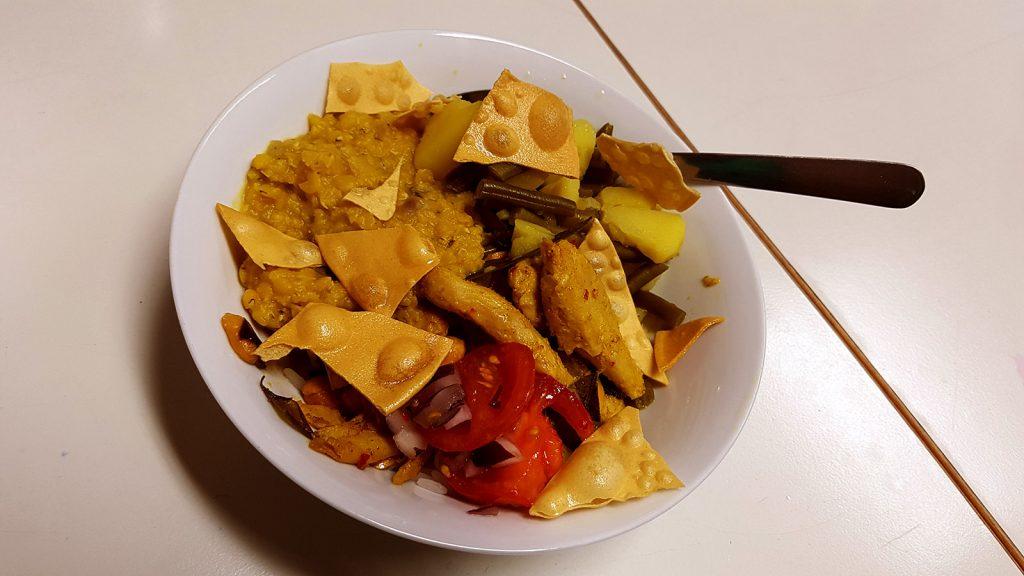 Ein voller Teller mit Tomaten, Hühnchen und Soße möchte verzehrt werden.