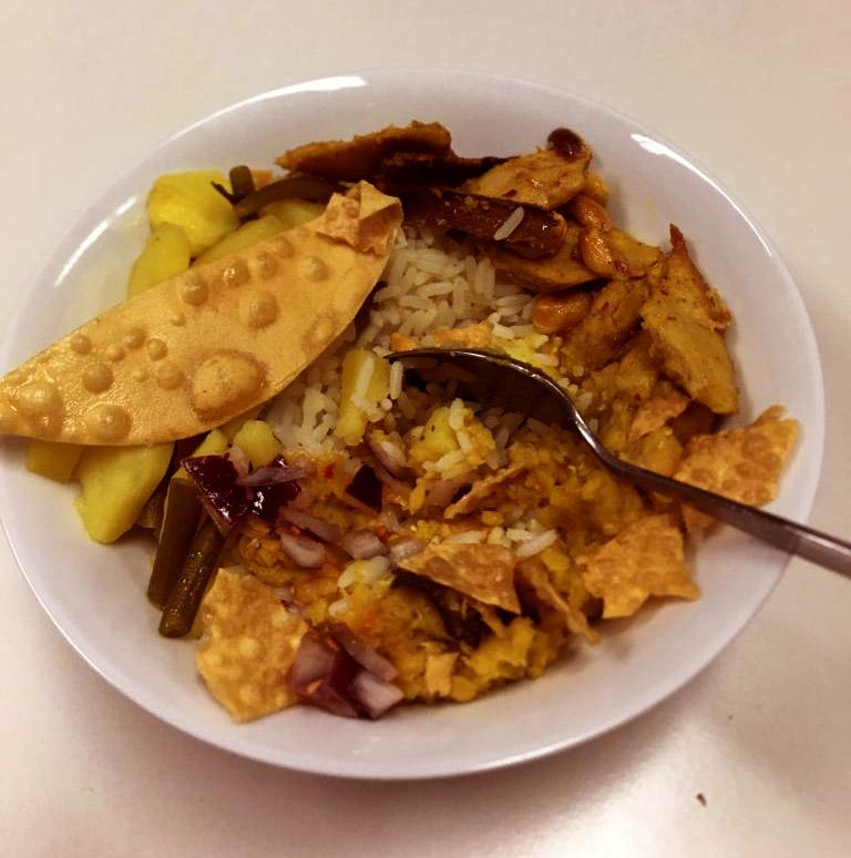 Ein voller Teller mit gekochten Kartoffeln, Reis und allerlei Gemüse. Ein Löffel steckt schon drin und das Essen wartet drauf verputzt zu werden.