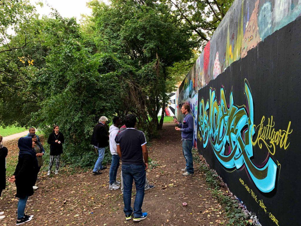 Der Gruppenleiter erklärt die Kunst des Graffitis der aufmerksam lauschenden Menge.