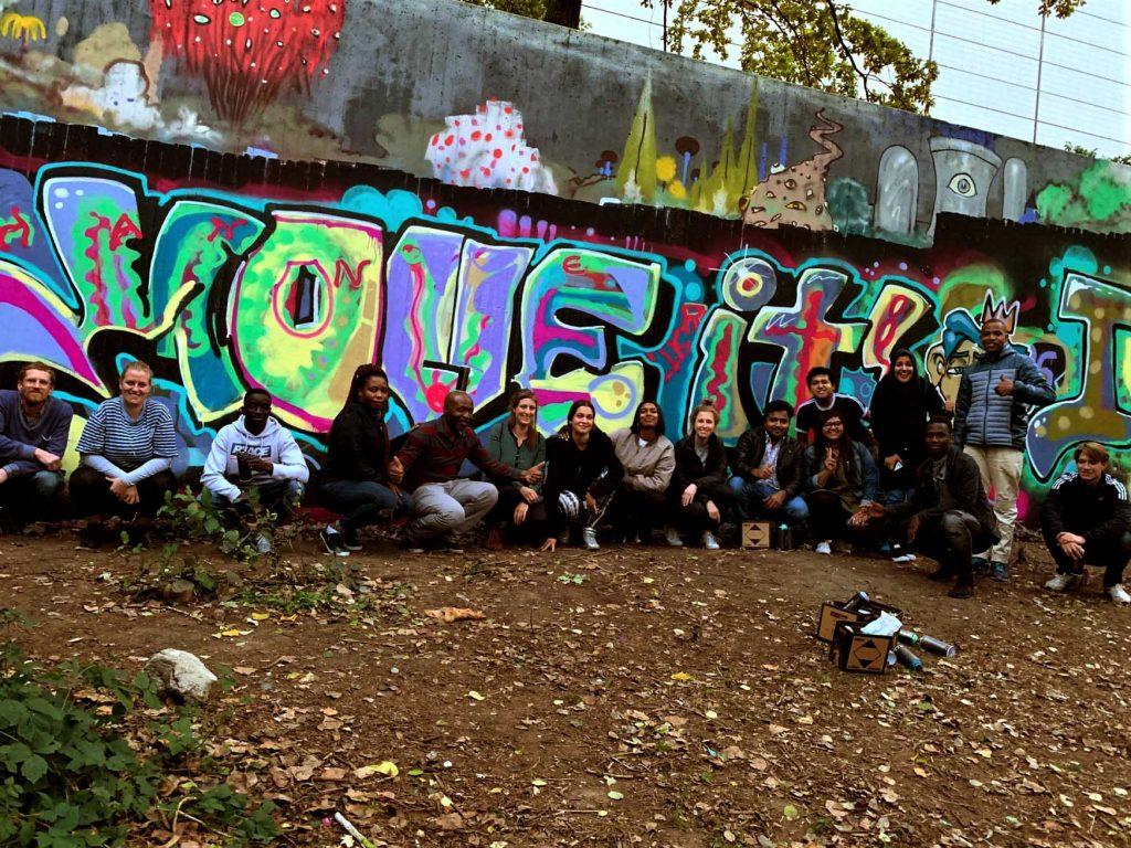 Die ganze Gruppe posiert stolz vor dem vollendeten Kunstwerk - dem riesigen bunten Schriftzug