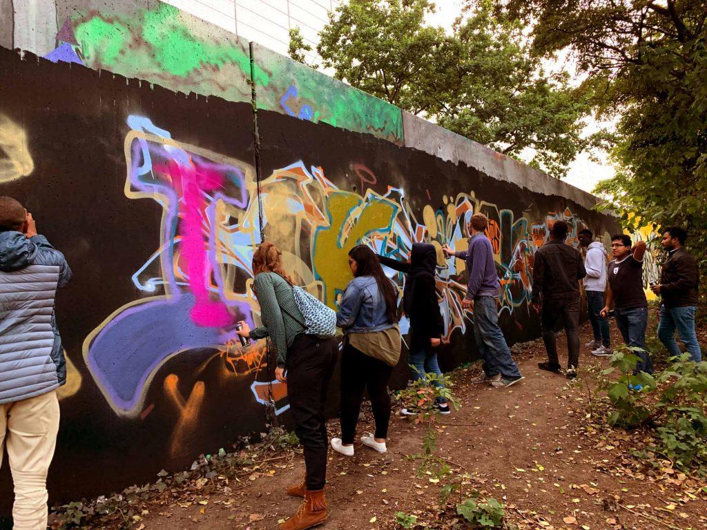 Viele Leute stehen vor einer langen Mauer und sprühen alle zusammen mit Spraydosen Farbe auf ein großes Bild, das langsam Gestalt annimmt.