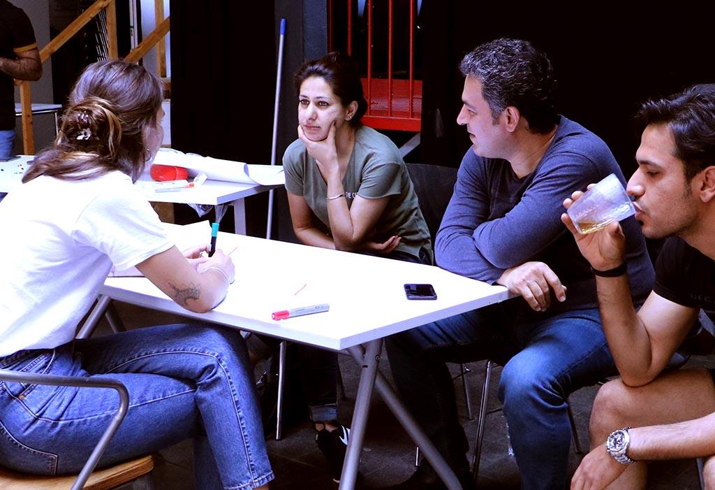 Zwei Frauen diskutieren, während ein Mann aufmerksam zuhört.