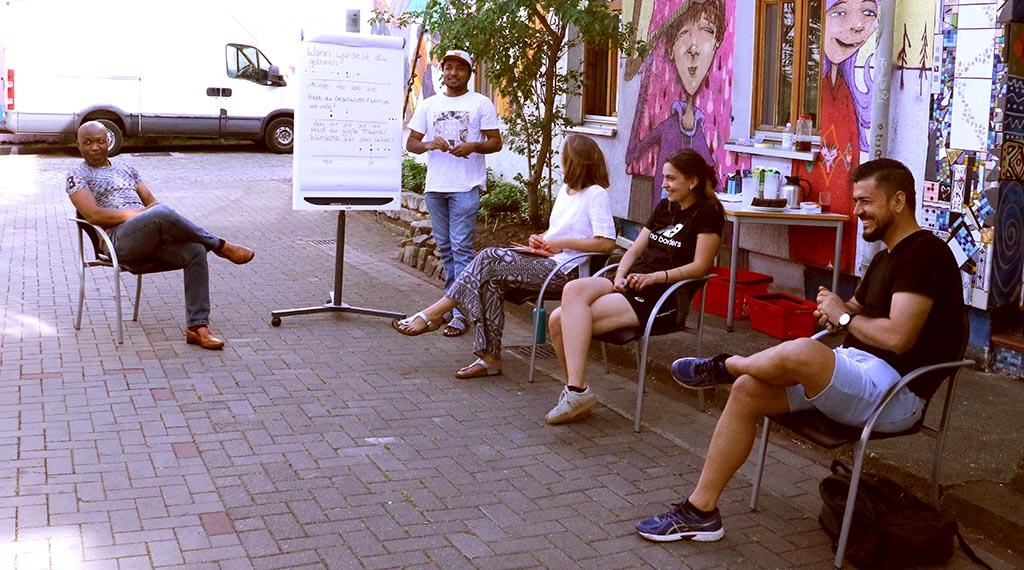 Die Gruppe lauscht der Präsentation eines jungen Mannes.