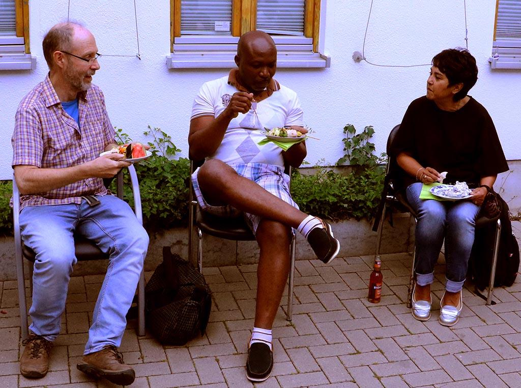 Zwei Männer und eine Frau sitzen, essen und reden miteinander.